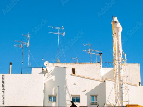 Foto Azoteas blancas de casas con antenas y cielo azul en una localidad del mediterrá