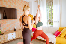 Flexible Female In Activewear Doing Yoga In Crescent Lunge On Knee Pose With Help Of Plump Instructor At Home