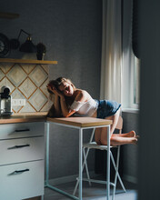 Attractive Dreamy Female In White Top With Bare Shoulders And Looking At Camera While Leaning On Kitchen Counter