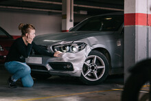 Side View Of Upset Young Lady In Casual Clothes Sitting On Knees And Touching Damaged Car Headlights After Accident In Parking Space