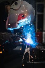 Side View Of Unrecognizable Repairman In Protective Helmet Using Torch While Welding Metal Details During Work In Garage