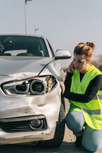 Unhappy Young Female Driver In Yellow Road Safety Vest Having Phone Conversation And Checking Damages On Modern Car Parked On Pavement After Crash