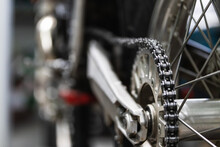 Wheel Of Vintage Motorcycle With Chrome Details And Chain Placed On Platform Lift During Maintenance In Garage