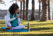 Happy Brazilian Female Browsing Smartphone And Enjoying Music In Earphones While Sitting With Crossed Legs In Lawn After Yoga