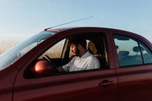 Bearded Young Male Driver In White Shirt Sitting In Car Parked On Roadside In Countryside