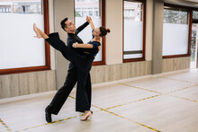Skilled Couple Of Dancers In Elegant Clothes Rehearsing Moves Of Ballroom Dance During Class In Studio