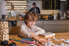 Cheerful Boy Mixing Dominoes Near Marker Pens And Book On Table Against Parents Cooking Lunch In Kitchen At Home