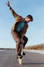 Full Body Young Bearded Male Skater Standing On Edge Of Skateboard Keeping Balance While Performing Trick On Asphalt Road With Hand Raised And Looking Down