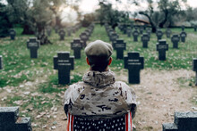 Back View Of Soldier In Uniform Sitting On Chair With American Flag While Mourning Death Of Warriors At Graveyard