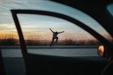 From Car View Of Full Body Young Man In Casual Wear Jumping On Skateboard While Performing Kickflip On Asphalt Road Against Dusky Sky