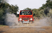 Unrecognizable Man Driving Red SUV Vehicle On Dirt Road With Water Puddle Among Green Trees In Summer Countryside
