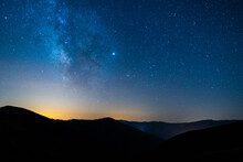Picturesque View Of Starry Blue Sky With Clouds Over Mount With Mountains Silhouettes At Sunset
