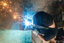 Unrecognizable Male Master In Protective Helmet Welding Metal Piece At Workbench In Workshop