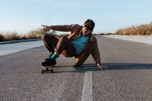 Full Body Young Bearded Male Skater In Casual Clothes Performing Trick Touching Ground While Riding On Asphalt Road