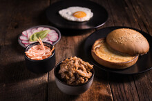 High Angle Set Of Ingredients For Pulled Pork Hamburger With Vegetables And Fried Egg Arranged On Wooden Table