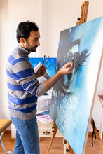 Side View Of Young Bearded Ethnic Painter In Casual Wear Painting With Brush On Canvas In Art Studio