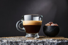 Transparent Glass Of Strong Black Coffee With Foam Near Bowl Of Brown Sugar Cubes On Black Background