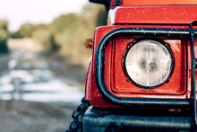 Closeup Of Headlight Of Red SUV Vehicle Parked On Wet Dirt Path Among Green Trees In Countryside