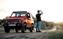Full Body Back View Of Unrecognizable Male Adventurer Standing Near Red Off Road Car Parked On Dirt Road Among Forest And Looking Away Thoughtfully While Enjoying Summer Journey In Countryside