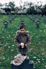 High Angle Of Small Kid Mourning Death Of Soldier Fighting In War At Graveyard