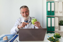 Elderly Male Orthodontist Showing Green Apple Against Portable Computer While Taking On Video Call In Clinic