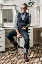 Trendy Mature Hipster Businessman In Eyewear And Trendy Clothes Looking Away On Chair In House