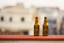 Pair Of Beer Bottles On Balcony Wall At Sunset
