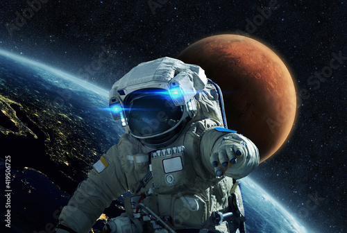 Space man in a space suit flies in open space on a background of the blue planet earth and the red planet Mars Fototapet