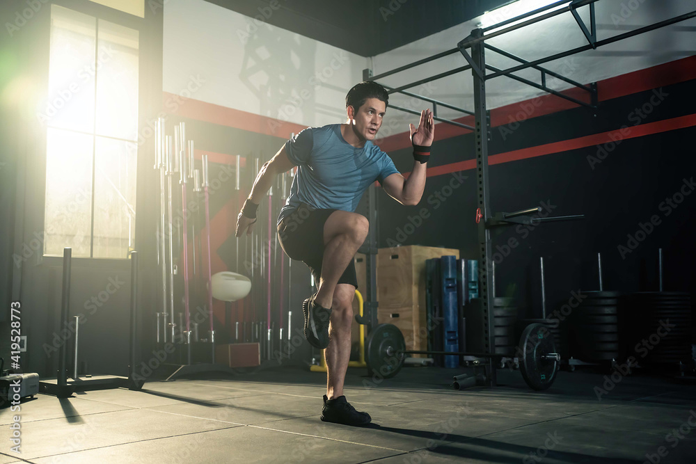 Fototapeta Caucasian young man doing cardio exercise by high knees pose in gym.