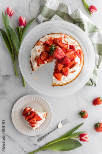 Canvas-taulu Top down view of a strawberry shortcake with one slice served on a small plate beside and tulips surrounding