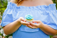 A Plump Girl In A Spring Blooming Park Holds A Cupcake In Her Hands. Plus-size Girl And Sweet.