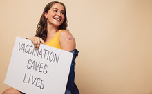 "Cheerful Woman With A Signboard Of ""vaccination Saves Lives"""