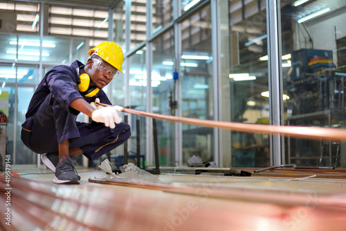 Canvastavla African American mechanic engineer worker is choosing copper tube for sawing whi