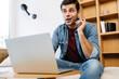 Leinwandbild Motiv Excited young man pointing finger upward while working with laptop