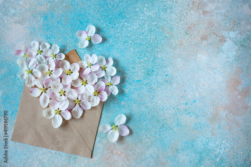 Fototapeta Spring background with envelope and flowers of apple tree in the shape of a heart, colored space for text. obraz