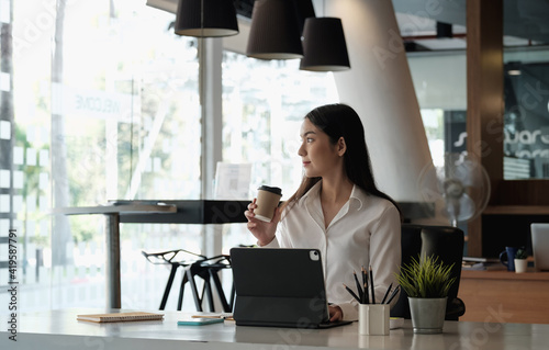Fotografia Portrait of beautiful woman or accountant sitting at desk in modern office with interior drinking hot beverage holding cup with coffee in hands looking outside enjoying freetime