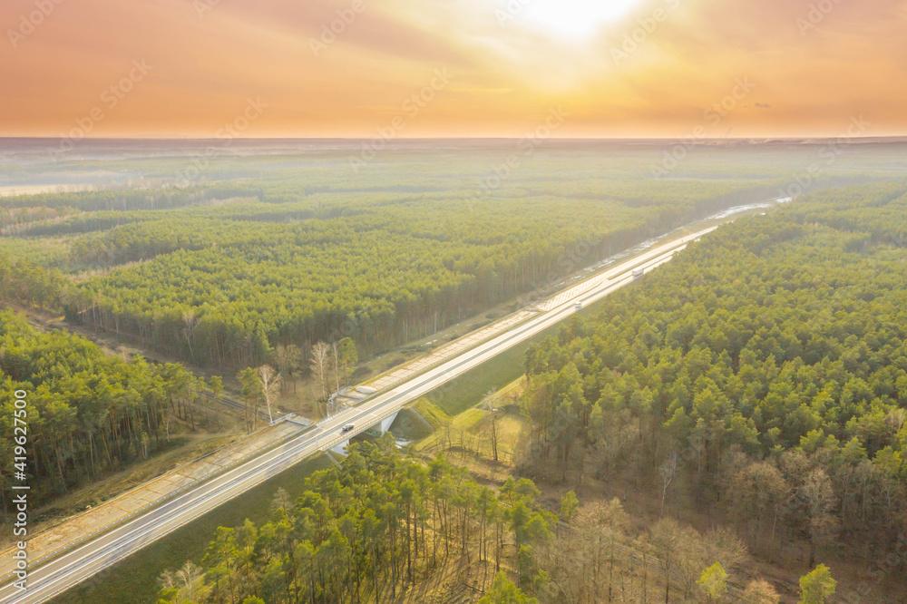 Fototapeta Betonowa, dwupasmowa droga w świetle zachodzącego słońca. Zdjęcie z drona.