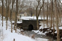 The Stone Bridge From The Forest On A Cold Winter Day.