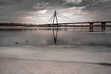 Romantic View Of The Kiev's Pivnichnyi (ex Moskovsky) Bridge , Over The Frozen Dnieper River. The Sky Is Covered By Dramatic Pink And Gray Clouds During The Cold Winter Days