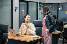 Asian Businesswoman Consulting With Happy And Smiling Colleague Wearing Face Shield At Desk In Modern Office