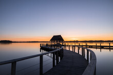Swinged Pier Construction And Shelter With Thatched Roof At Beautiful Colorful Sunrise Under Clear Sky At Lake Hemmelsdorf, Schleswig-Holstein, Northern Germany