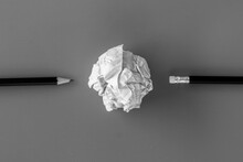 White Paper Ball With A Black Pencil On A White Background.