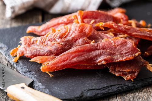 Foto Dried chicken meat. Tasty jerky meat.
