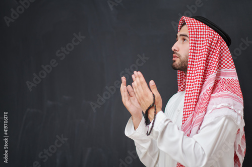 Arab man in traditional clothes praying to God or making dua Fototapeta