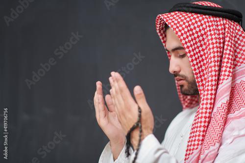 Fotografija Arab man in traditional clothes praying to God or making dua