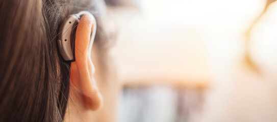 Deaf woman wearing hearing aid. Digital hearing aid in woman's ear. Brunette Woman with Modern Hearing Aid. Hearing Impaired.