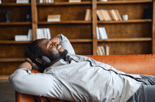 Calm African Guy In Headphones Enjoying Music Lying On The Couch, A Multiracial Guy Put His Hands Behind His Head, Smiles And Dreaming With Eyes Closed, Relaxing And Feels Happy