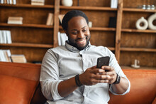 Cheerful African-American Guy Enjoys Messaging On The Smartphone Sitting On The Couch, A Guy Typing On The Phone, Chatting Online, Smiles