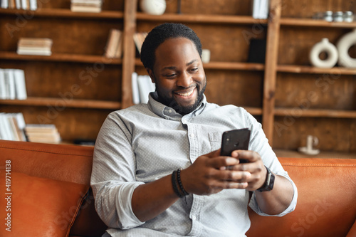 Fototapeta Cheerful African-American guy enjoys messaging on the smartphone sitting on the couch, a guy typing on the phone, chatting online, smiles obraz