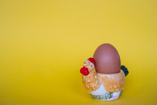 Natural Brown Egg In Colorful Easter Eggcup On Yellow Background. Easter Egg Theme.